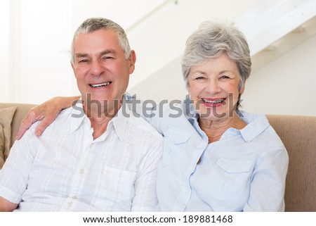 Retired couple sitting on couch smiling at camera at home in living room - stock photo