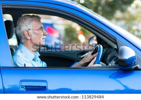 Retired elder man driving a blue car - stock photo