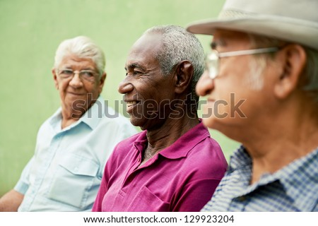 retired elderly people and free time, group of happy senior african american and caucasian male friends talking and sitting on bench in park - stock photo