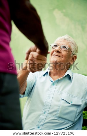 retired elderly people and free time, happy senior african american and caucasian male friends greeting and sitting on bench in park - stock photo