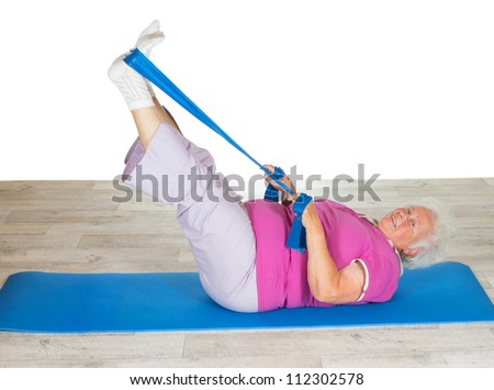 Retired lady doing exercises lying on a gym mat raising her legs in the air to strengthen her abdominal muscles - stock photo