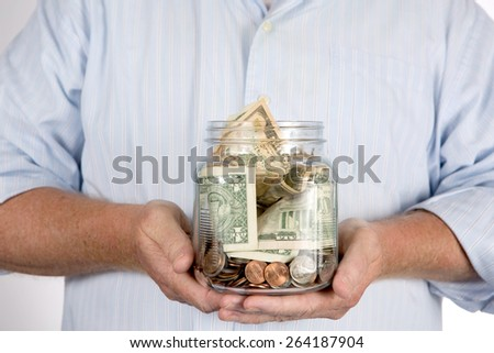 Retired man holding his retirement piggy bank money account in his hands in a glass jar. - stock photo