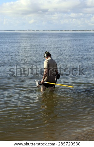 Retired man is searching for rings & other jewelry in the water, many people lose their jewelry in the lakes & oceans the water when they become loose because the water temperature contract the skin - stock photo