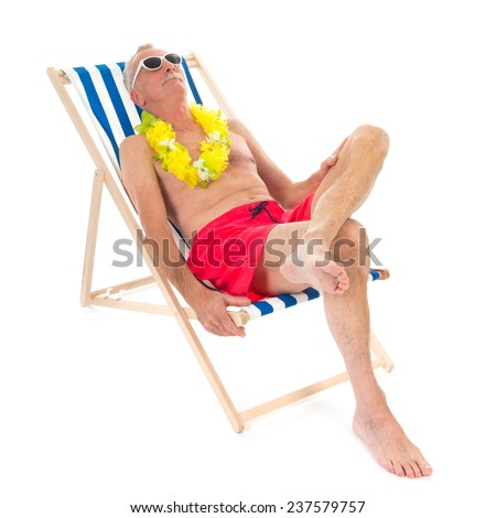 Retired man on vacation sitting in beach chair drinking beer
