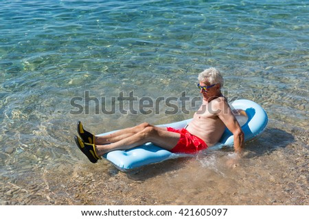 Retired man playing with inflatable bed floating in the sea