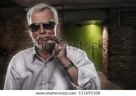 Retired man with strong personality standing in the darkness in sunglasses puffing on a big cigar, quintessential stereotype of a retired successful executive - stock photo