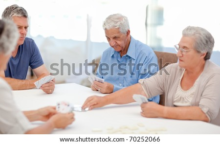 Retired people playing cards together at home - stock photo