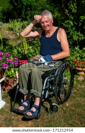 Retired person in a wheelchair starts to sweat during gardening. - stock photo
