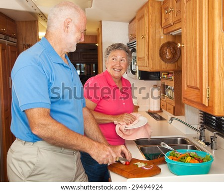 Retired senior couple in the kitchen of their RV camper. - stock photo