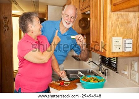Retired senior couple making lunch in their motor home kitchen.  The husband can't wait for lunch.