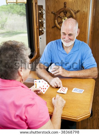 Retired senior couple playing a game of cribbage in the kitchen of their motor home. - stock photo