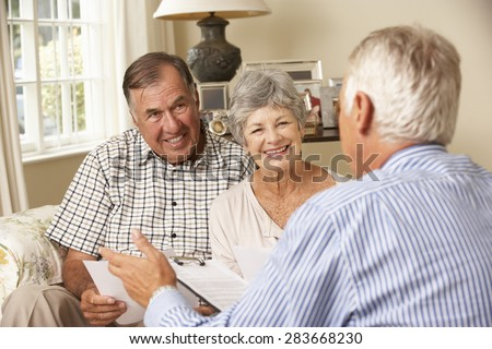 Retired Senior Couple Sitting On Sofa Talking To Financial Advisor - stock photo