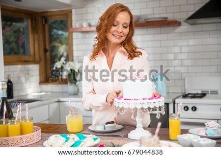 retired woman at kitchen home decorating house for a party family gathering with cake