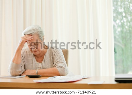 Retired woman calculating her domestic bills - stock photo