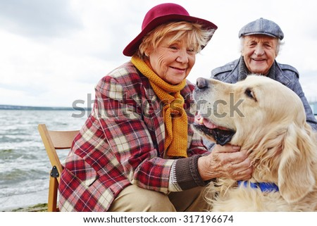 Retired woman cuddling cute pet with her husband on background - stock photo
