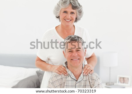 Retired woman giving a massage to her husband at home - stock photo