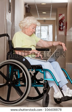 Retired woman on wheelchair using laptop. - stock photo