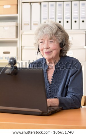 Retired woman smiling into the webcam of a notebook, copy space - stock photo