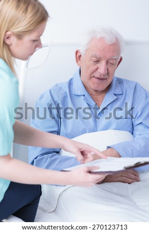Retiree lying in hospital bed talking with doctor