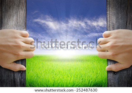Retirement concept. Hand opening an old wooden door and found a texts floating over green field and bright blue Sky Sunrise. - stock photo