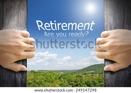 "Retirement concept. ""Retirement are you ready"" word floating in the sky while 2 hands opening a wooden door to the new world. - stock photo"