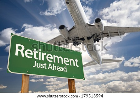 Retirement Green Road Sign and Airplane Above with Dramatic Blue Sky and Clouds. - stock photo