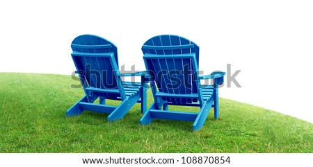 Retirement Planning symbol with two empty blue adirondack lawn chairs sitting on green grass as a financial concept of future successful investment strategy on a white background. - stock photo