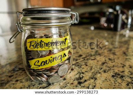 "Retirement Savings Money Jar. A clear glass jar filed with coins and bills, saving money. The words ""Retirement Savings"" written on the outside."