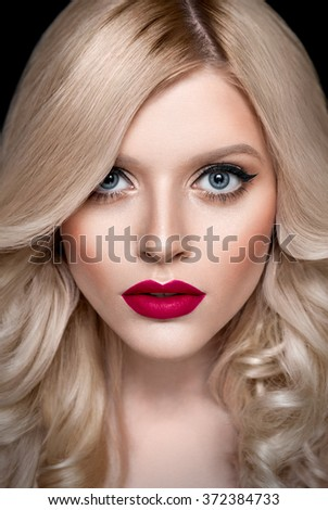 Retouched studio beauty portrait of a blonde caucasian girl with curly hair, bright make up on dark background