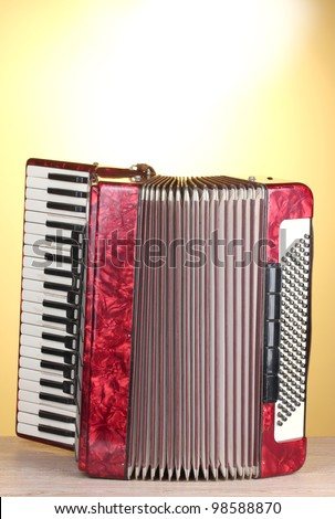 Retro accordion on wooden table on yellow background - stock photo