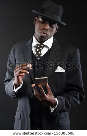 Retro african american gangster man wearing striped suit and tie and black hat. Taking cigarette out of silver box. Studio shot. - stock photo