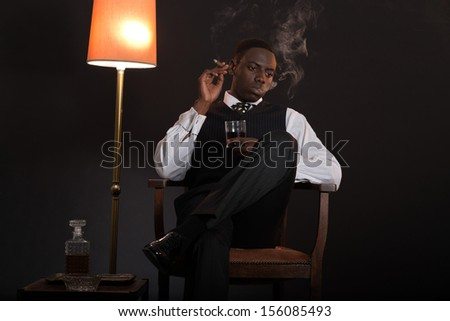 Retro african american gangster man wearing striped suit and tie. Sitting in a chair in living room. Smoking cigar. Holding glass of whisky.