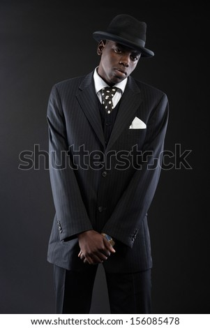 Retro african american gangster wearing striped suit and tie and black hat. Studio shot.