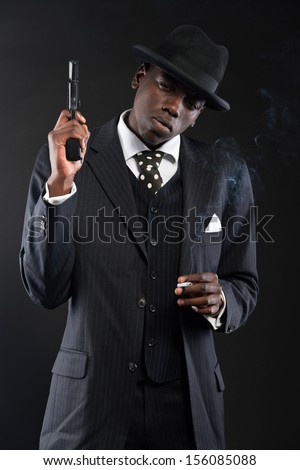 Retro african american mafia man wearing striped suit and tie and black hat. Holding a gun. Smoking cigarette. Studio shot.
