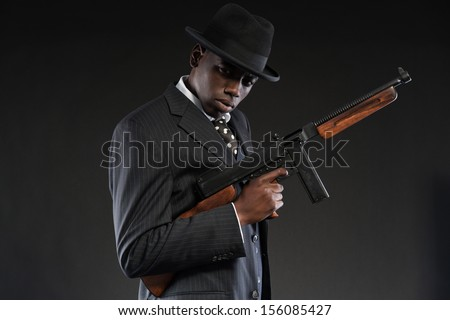 Retro african american mafia man wearing striped suit and tie and black hat. Holding machine gun. Studio shot.