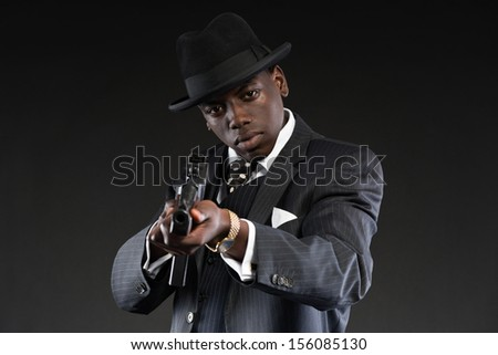 Retro african american mafia man wearing striped suit and tie and black hat. Shooting with machine gun. Studio shot.