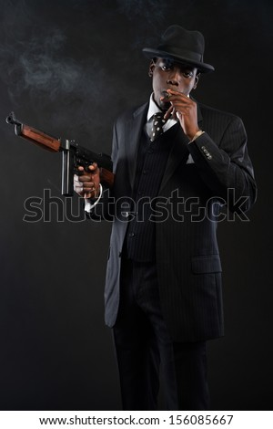Retro african american mafia man wearing striped suit and tie and black hat. Smoking cigar. Holding a gun. Studio shot.