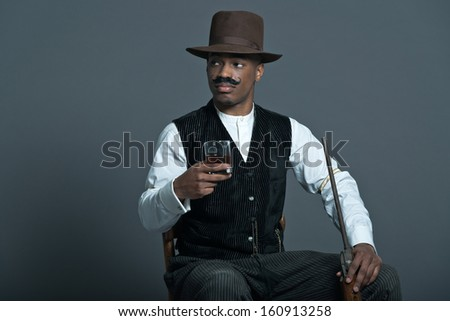 Retro afro america western cowboy man with mustache. Drinking whiskey. Sitting in wooden chair holding a rifle. Wearing brown hat. Cool tough guy. - stock photo