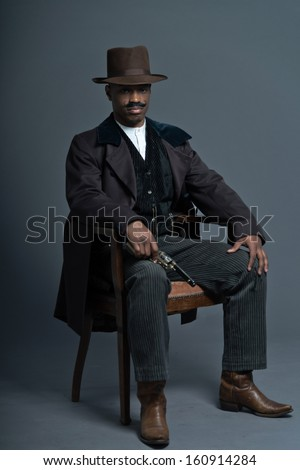 Retro afro america western cowboy man with mustache. Sitting in wooden chair holding a gun. Wearing brown hat. Cool tough guy. - stock photo