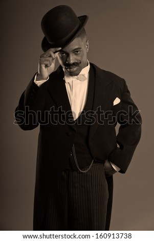 Retro afro american 1900 style man with mustache. Wearing black hat. Taking off his hat.