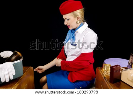 Retro Airline Stewardess or Flight Attendant Removing Her Jacket After Work. - stock photo