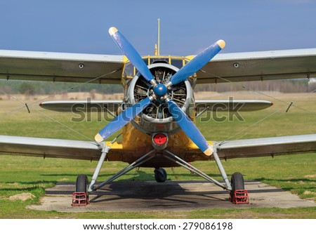 Retro airplane on green grass. Frontal view of the propeller engine and cockpit. - stock photo