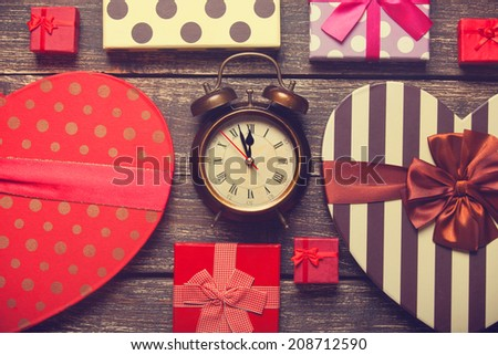 Retro alarm clock and christmas gifts around - stock photo