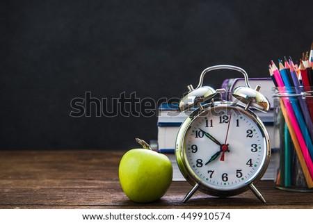 retro alarm clock and classroom chalkboard, back to school concept - stock photo