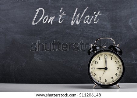 "Retro alarm clock and text ""Don't Wait"" written with chalk on the blackboard."