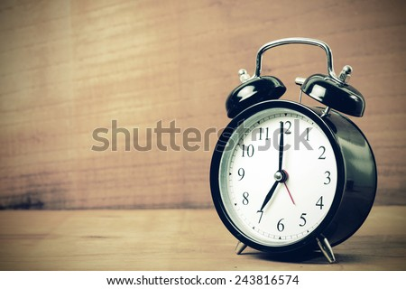 Retro alarm clock at 7 o'clock with wooden background, vintage tone  - stock photo