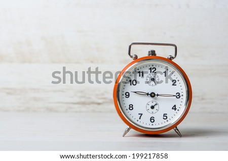 Retro alarm clock on a table - stock photo