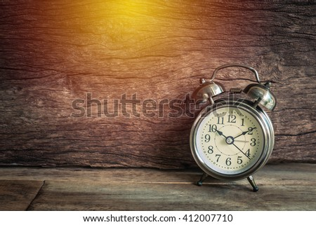 Retro alarm clock on a table made with retro color image style - stock photo