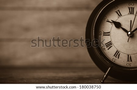Retro alarm clock on a table. Photo in retro color image style - stock photo