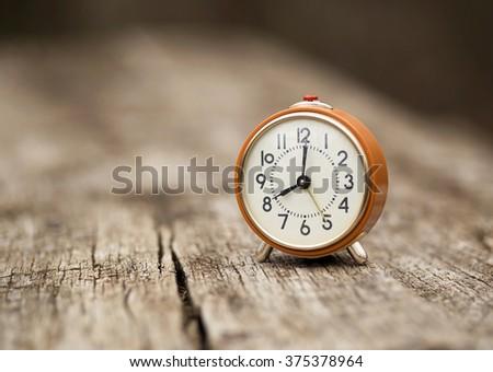 Retro alarm clock on a wooden table - stock photo